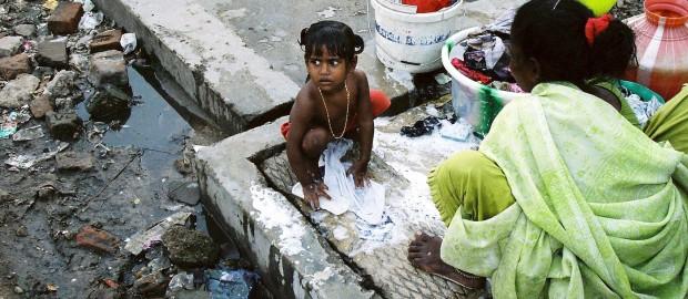 Kleines Mädchen beim Wäschewaschen in einem indischen Slum. Foto: Petra Welzel